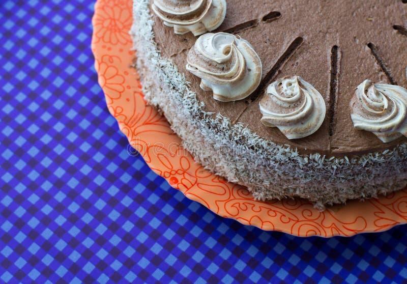 Torta de chocolate en la placa anaranjada en fondo azul imagen de archivo