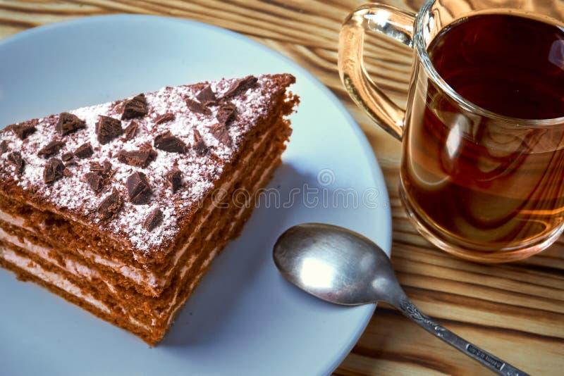 Torta de chocolate en una placa, taza de té negro caliente imagen de archivo libre de regalías