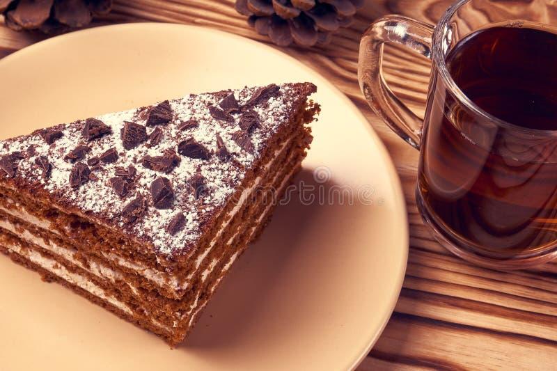 Torta de chocolate en una placa, taza de té negro caliente foto de archivo