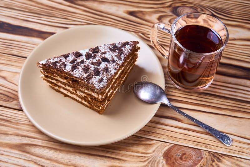 Torta de chocolate en una placa, taza de té negro caliente, cuchara imágenes de archivo libres de regalías