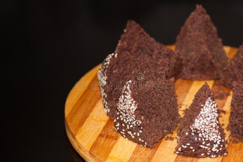 Torta de chocolate hecha en casa con las semillas de sésamo, cortadas en un tablero foto de archivo libre de regalías