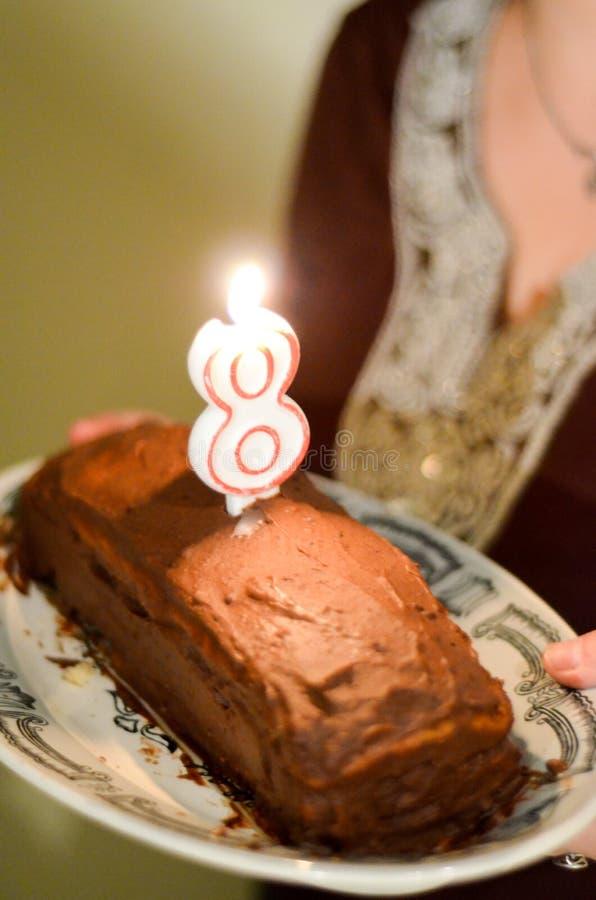 Torta de chocolate de ocho cumpleaños con la vela en la placa fotografía de archivo