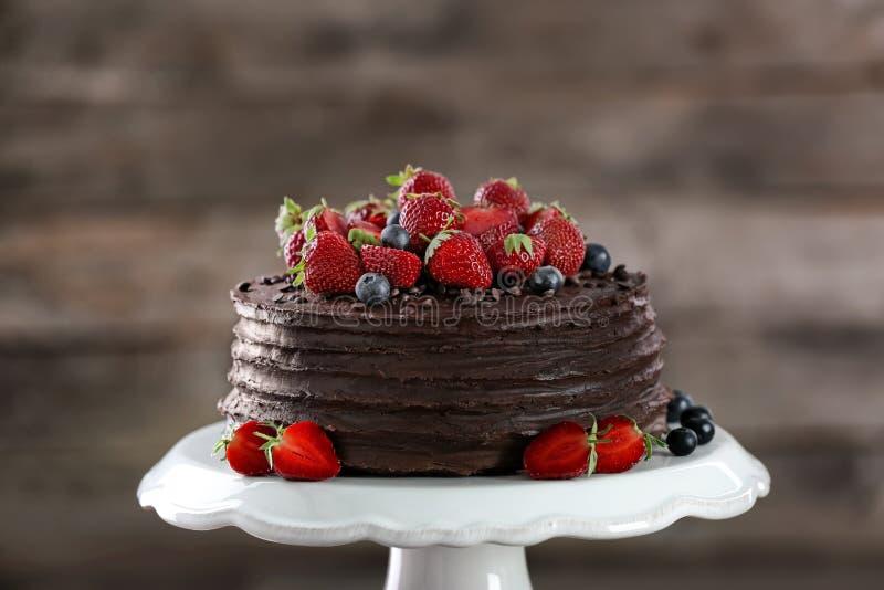Torta de chocolate sabrosa adornada con la fresa y el arándano en soporte del postre imagen de archivo