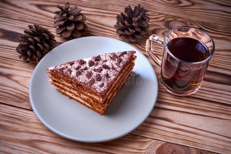 Torta de chocolate una placa, taza de té negro caliente, conos del cedro foto de archivo