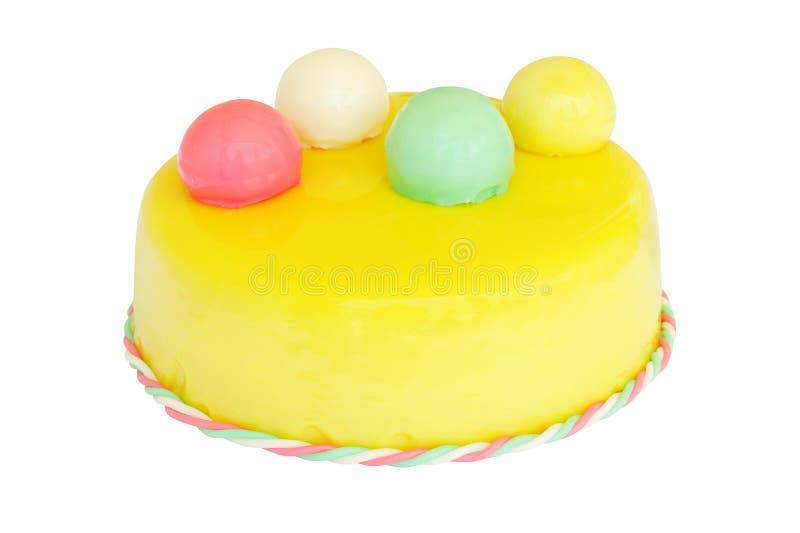 Torta de cumpleaños amarilla con las bolas coloreadas aisladas en blanco imagen de archivo