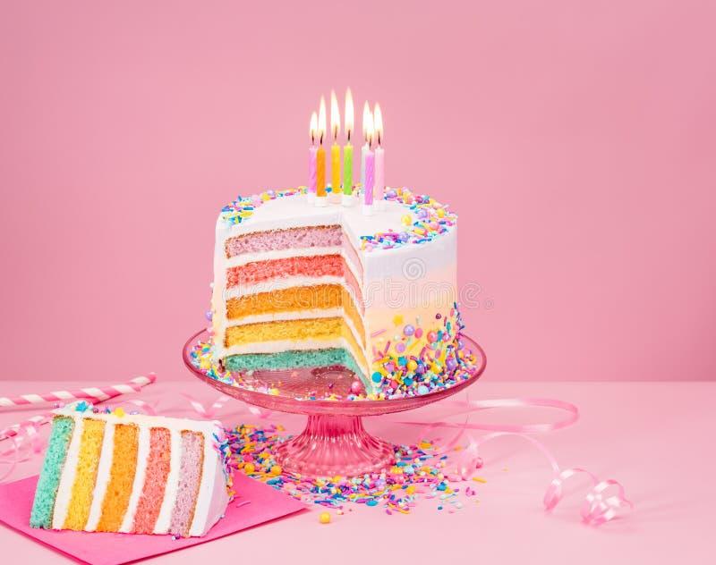 Torta de cumpleaños colorida sobre rosa foto de archivo