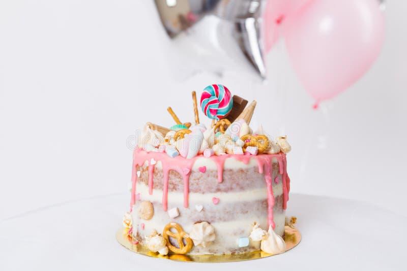 Torta de cumpleaños con adornado con los caramelos, piruleta, melcochas Color en colores pastel rosado Globos en fondo foto de archivo