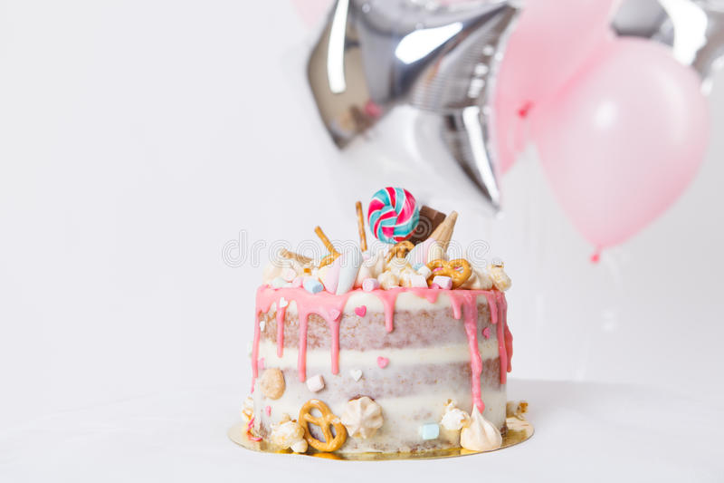 Torta de cumpleaños con adornado con los caramelos, piruleta, melcochas Color en colores pastel rosado Globos en fondo imagen de archivo