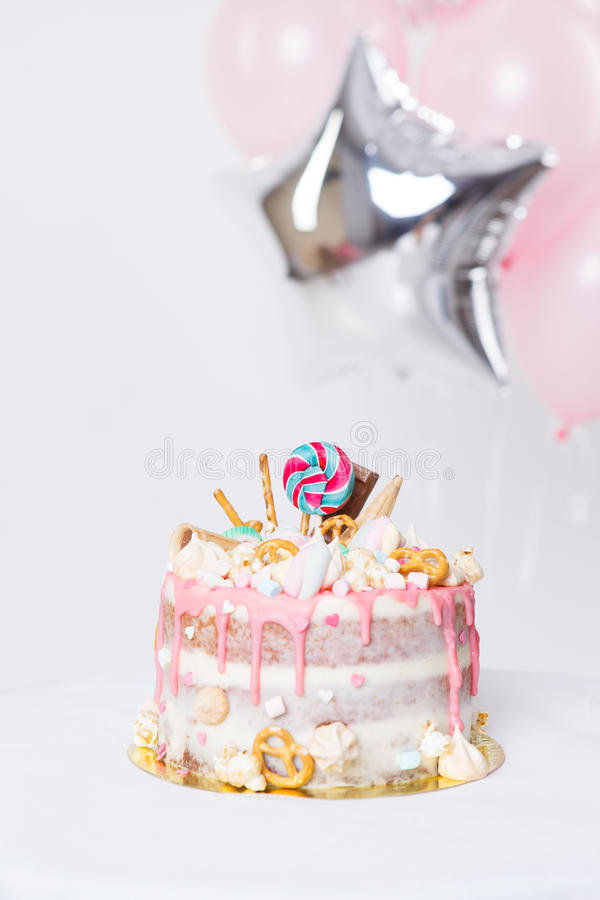 Torta de cumpleaños con adornado con los caramelos, piruleta, melcochas Color en colores pastel rosado Globos en fondo fotografía de archivo