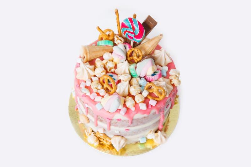 Torta de cumpleaños con adornado con los caramelos, piruleta, melcochas Color en colores pastel rosado Globos en fondo Aislado foto de archivo