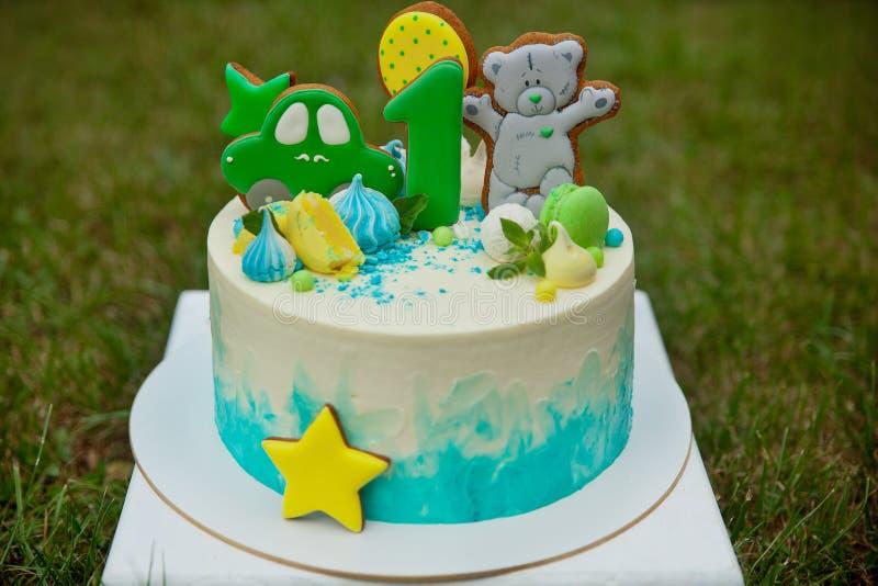 Torta de cumpleaños, con el número uno, y oso del pan de jengibre fotos de archivo