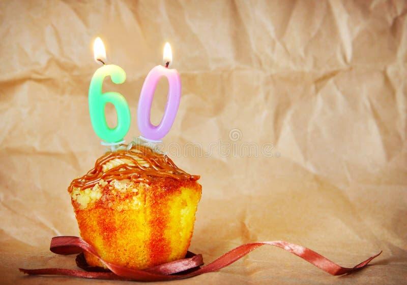 Torta de cumpleaños con las velas ardientes como número sesenta imagen de archivo libre de regalías
