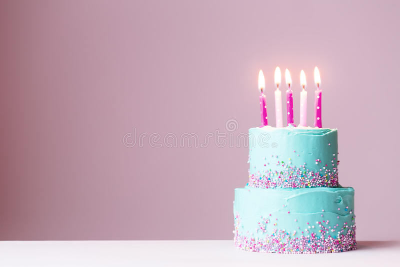 Torta de cumpleaños con las velas rosadas foto de archivo