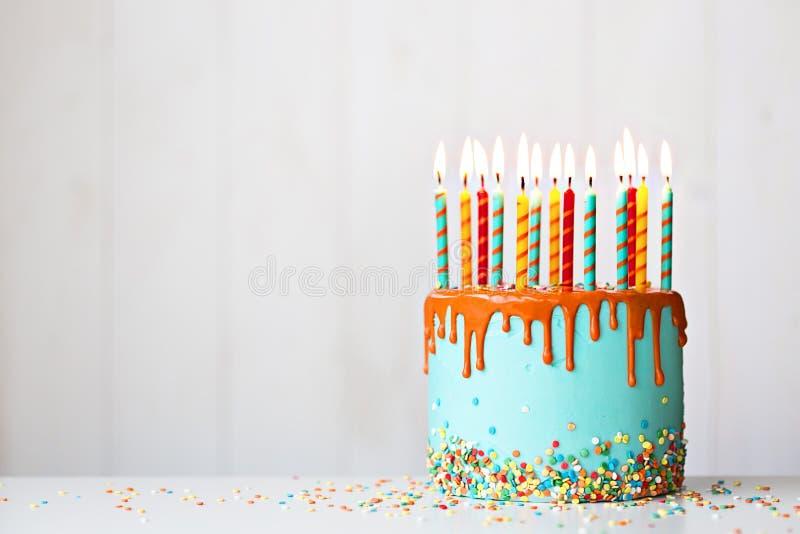 Torta de cumpleaños con velas y hielo de goteo imagenes de archivo