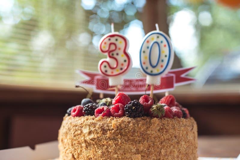 Torta de cumpleaños de la zarzamora de las frambuesas con las velas número 30 imágenes de archivo libres de regalías