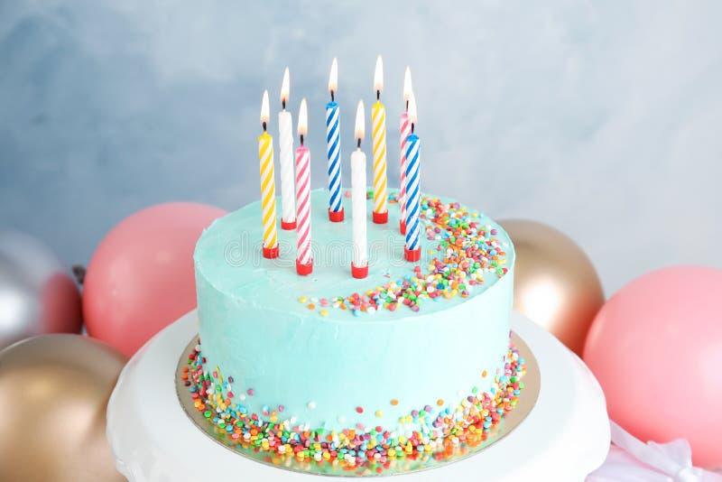 Torta de cumpleaños deliciosa fresca con las velas cerca de los globos foto de archivo