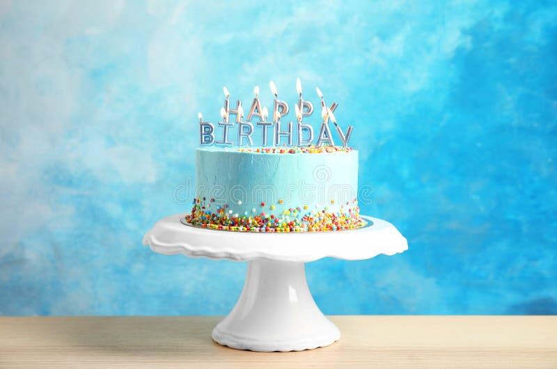 Torta de cumpleaños deliciosa fresca con las velas en soporte imagen de archivo