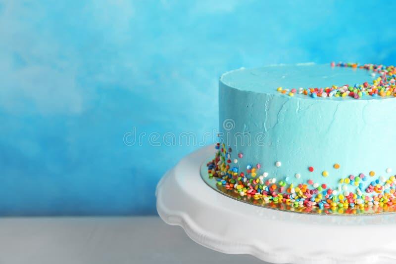 Torta de cumpleaños deliciosa fresca en soporte contra fondo del color foto de archivo libre de regalías