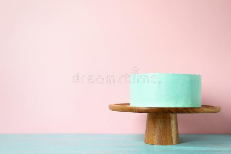Torta de cumpleaños deliciosa fresca en soporte contra fondo del color imagen de archivo