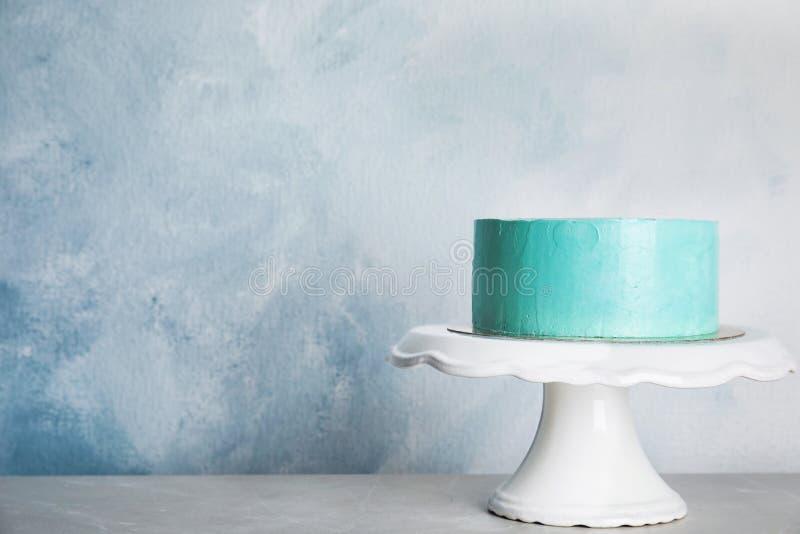 Torta de cumpleaños deliciosa fresca en soporte contra fondo del color fotografía de archivo