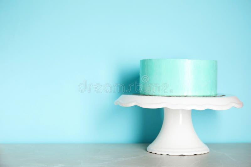 Torta de cumpleaños deliciosa fresca en soporte contra fondo del color fotos de archivo