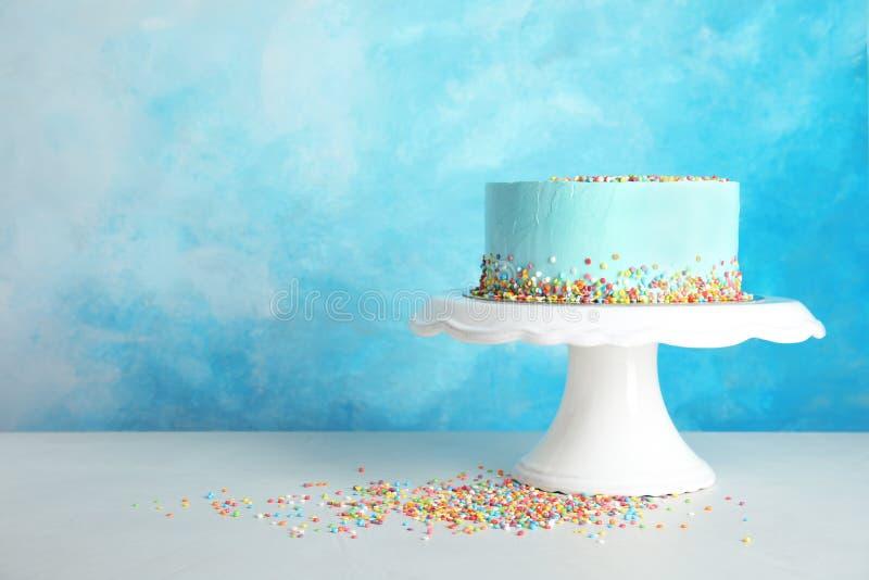 Torta de cumpleaños deliciosa fresca en soporte contra fondo del color fotos de archivo libres de regalías