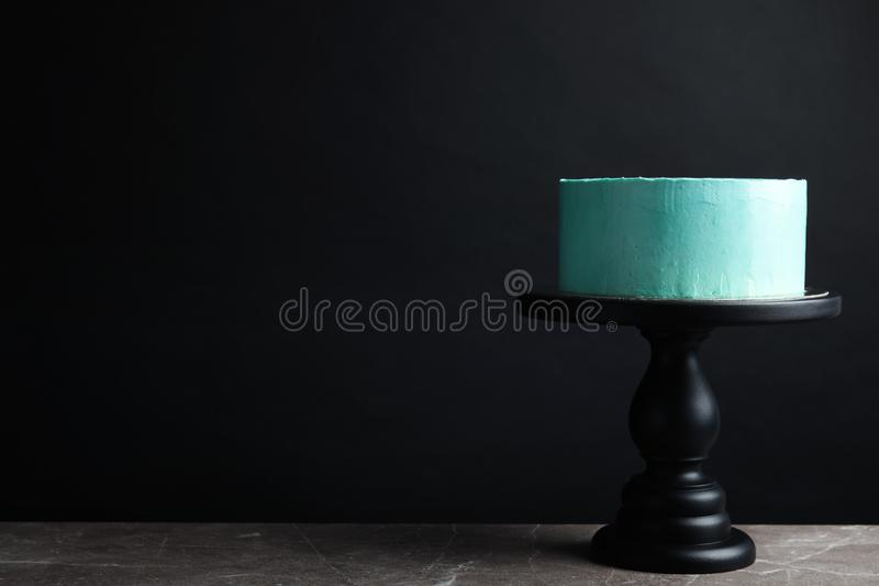 Torta de cumpleaños deliciosa fresca en soporte contra fondo negro foto de archivo