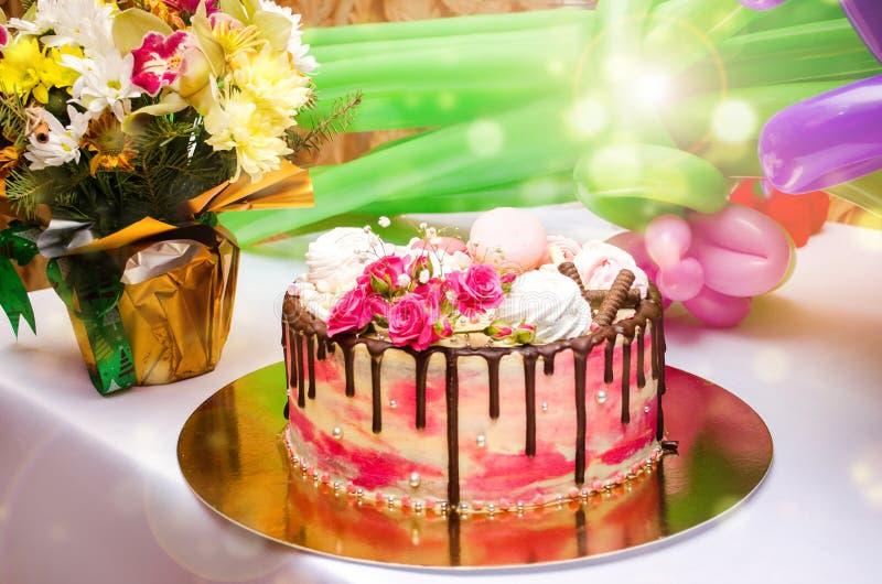 Torta de cumpleaños en el fondo brillante de la tabla imagenes de archivo