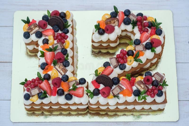 Torta de cumpleaños hermosa en la forma del número doce fotografía de archivo