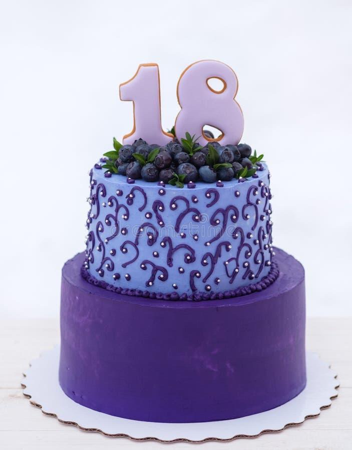 Torta de cumpleaños hermosa en tonos de la lila con el número dieciocho foto de archivo