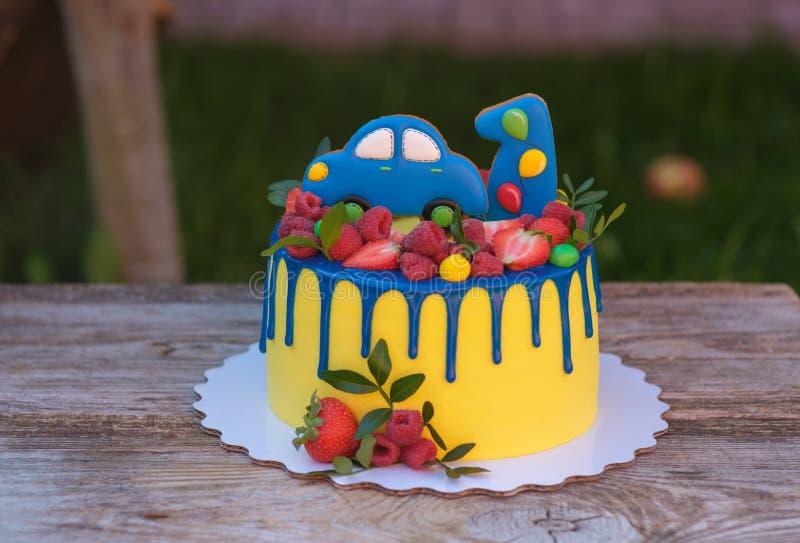 Torta de cumpleaños hermosa para un niño con un número uno y un coche imagenes de archivo