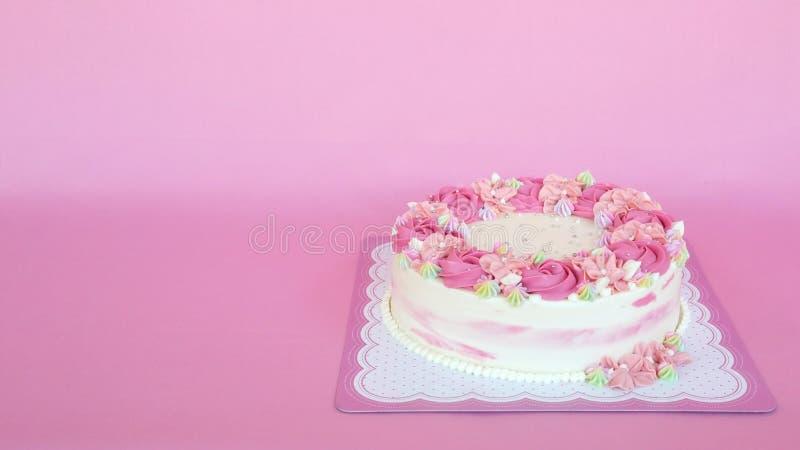 Torta de cumpleaños de la crema de las flores sobre fondo rosado fotos de archivo libres de regalías