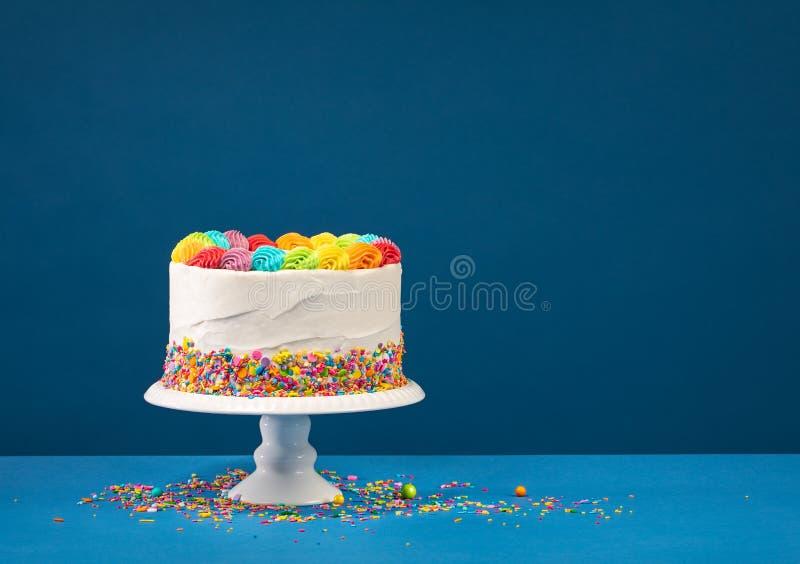 Torta de cumplea?os colorida sobre azul imagen de archivo libre de regalías