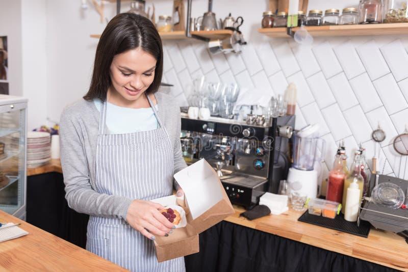 Torta de empaquetado sonriente hermosa de la mujer foto de archivo libre de regalías