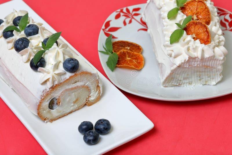 Torta de esponja cubierta con crema y adornada con los arándanos secados y las hojas de menta fresca Rebanadas también secas de n imagen de archivo libre de regalías