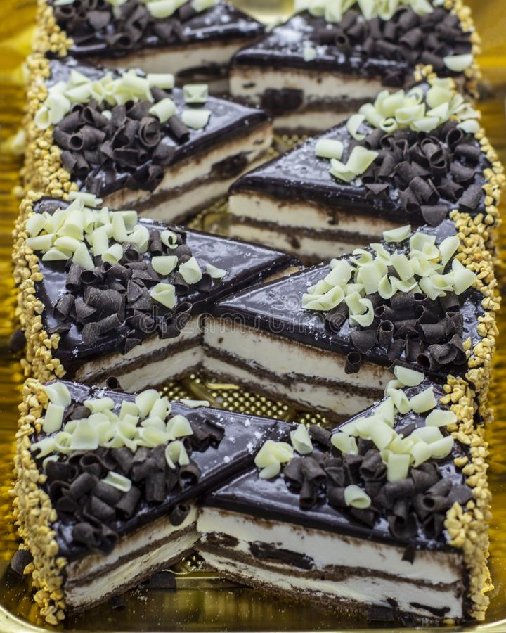 Torta de esponja del chocolate asperjada con los microprocesadores de chocolate blancos y oscuros Pedazos de torta en la ventana  fotografía de archivo libre de regalías