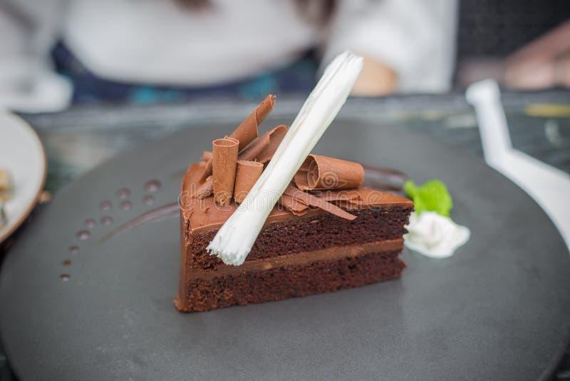 Torta de esponja del chocolate con el chocolate blanco del marrón el helar y del papel del buttercream del chocolate en el top fotos de archivo