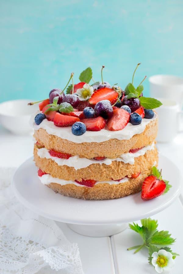 Torta de esponja del verano con las bayas poner crema y frescas imágenes de archivo libres de regalías