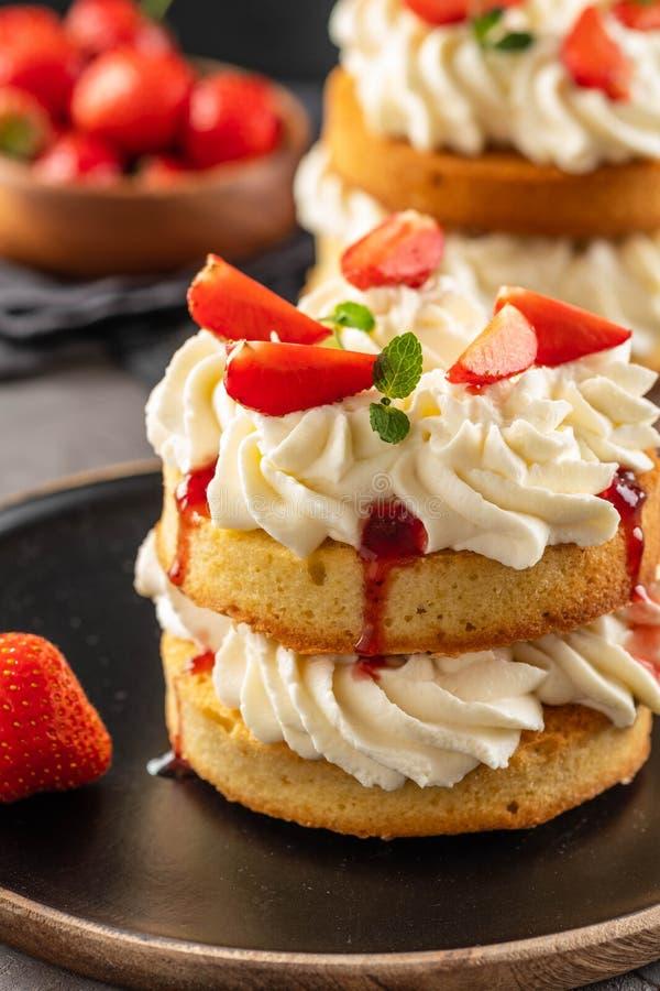 Torta de esponja de Victoria con las fresas, el atasco y la crema azotada en fondo oscuro Copie el espacio fotos de archivo libres de regalías