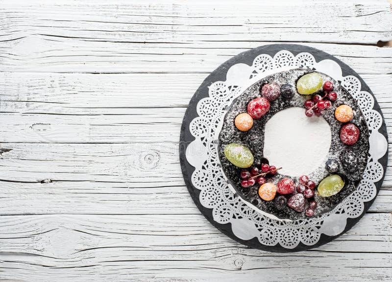 torta de la baya del chocolate en la placa sobre el fondo de madera blanco imagen de archivo