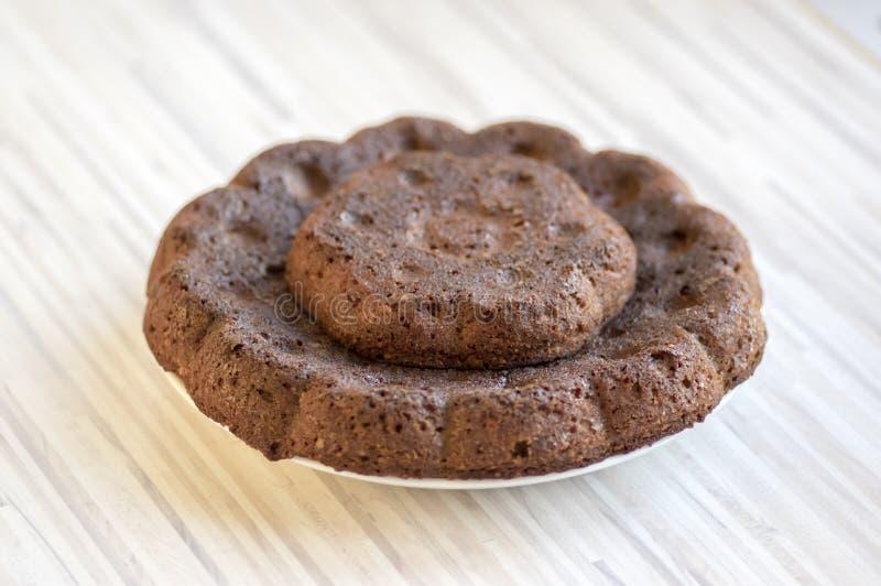 Torta de la calabaza de la almendra del chocolate en la placa blanca en la toalla de cocina colorida, galleta marrón oscura dulce foto de archivo libre de regalías