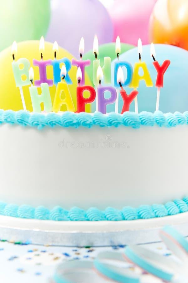 Torta de la celebración con las velas que deletrean feliz cumpleaños fotografía de archivo libre de regalías