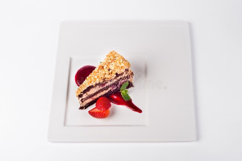 Torta de la cereza del chocolate con la fresa en el fondo blanco de la placa fotografía de archivo