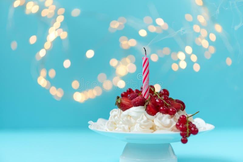 Torta de la fruta del cumpleaños de Pavlova con hacia fuera la vela soplada en fondo azul en colores pastel contra luces borrosas fotografía de archivo libre de regalías