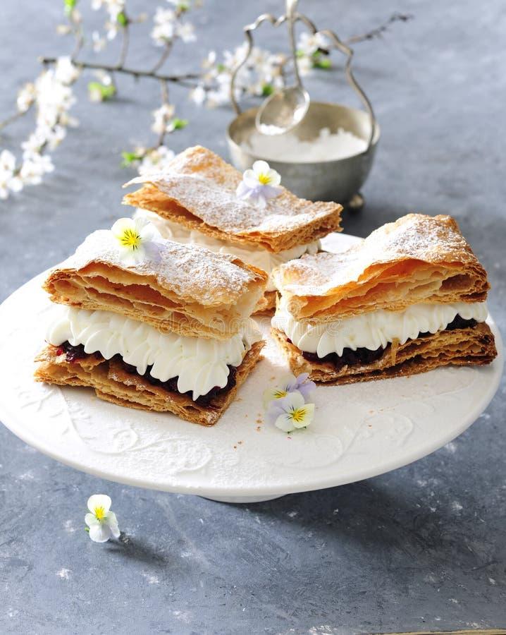 Torta de la pasta de hojaldre con los cotos azotados de la crema agria y de la cereza fotografía de archivo libre de regalías