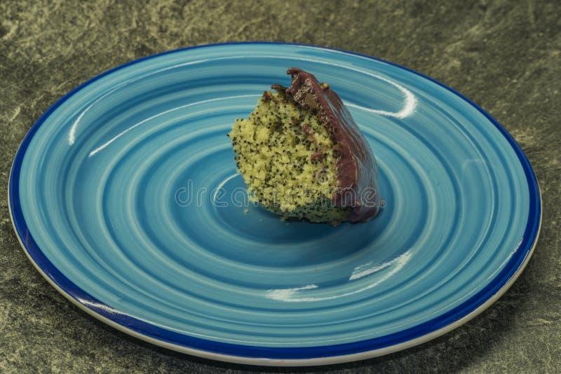 Torta de la semilla de amapola de la marijuana con el esmalte del chocolate y de la fruta en la placa azul foto de archivo