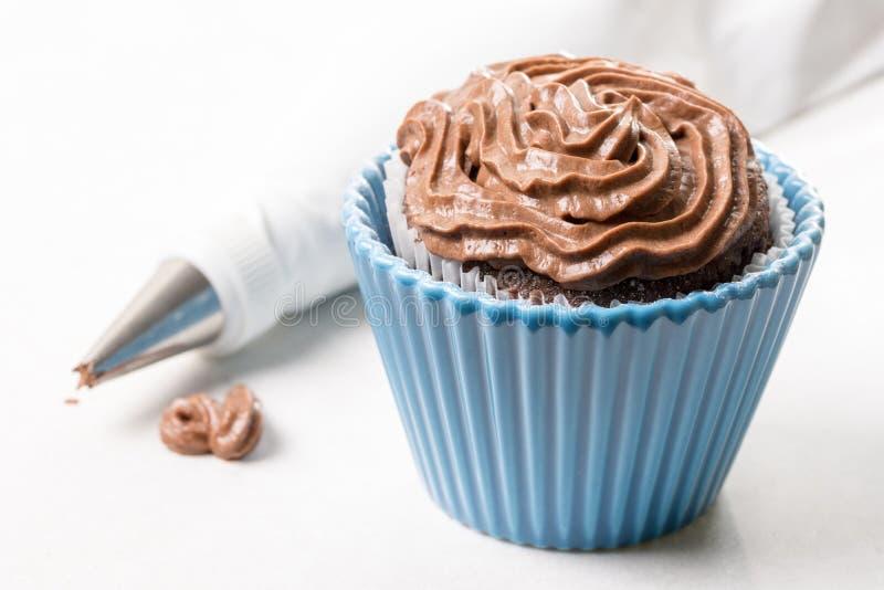 Torta de la taza del chocolate con crema del chocolate del ganache y bolso aflautado en el fondo en el fondo de mármol blanco imagenes de archivo