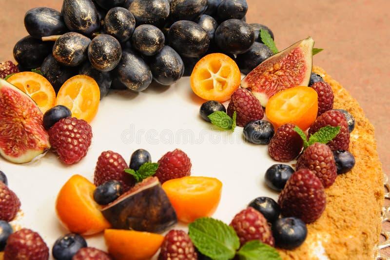 Torta de miel grande hermosa adornada con las frutas y las bayas en el top con el kandurin del oro de las peras y del espino cerv fotos de archivo