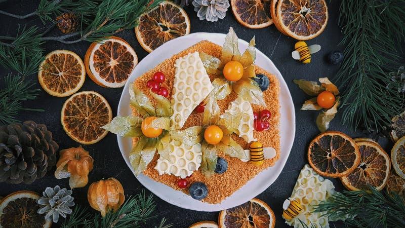 Torta de miel hecha casera, opinión superior sobre fondo oscuro, la decoración del Año Nuevo, naranjas de la Navidad y ramas del  fotos de archivo