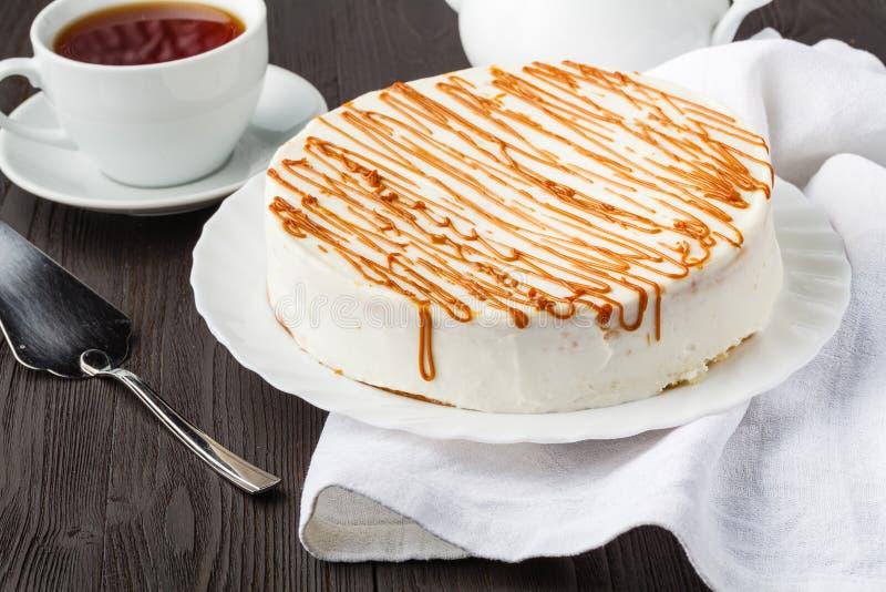 Torta de miel hecha en casa con crema agria en una tabla de madera con las pasas y las nueces fotos de archivo
